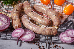 Raw sausages on the grill grate. Royalty Free Stock Photo