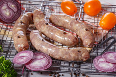 Raw sausages on the grill grate. Stock Photos