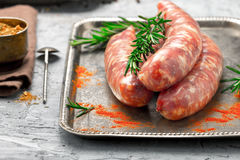 Raw sausages grilled on an iron tray close up Royalty Free Stock Images