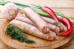 Raw sausages for grilling on a wooden board with spicy vegetables. Several raw sausages from pork with beef for grilling lie on a wooden board, close-up. Red Stock Photos