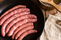 Raw sausages in iron cast pan, rice in copper pot, linen towel on wood kitchen table, top view Royalty Free Stock Photography