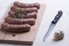 Raw sausages, knife and garlic on wooden table Royalty Free Stock Images