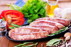 Raw sausages. On plate and on a table Stock Photos