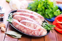 Raw sausages. On plate and on a table Royalty Free Stock Photography
