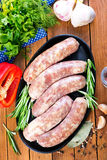 Raw sausages. On plate and on a table Stock Image