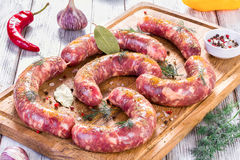 Raw sausages prepared for grill with chilli pepper, garlic, dill Royalty Free Stock Images
