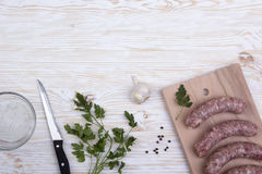 Raw sausages, salt, garlic and knife on wooden table Royalty Free Stock Images
