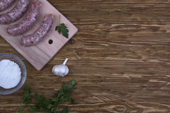 Raw sausages, salt and garlic on wooden table Stock Photos