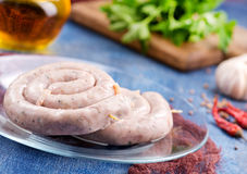 Raw sausages. With salt and spice on a table Stock Images