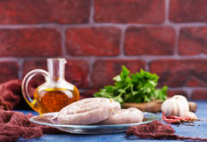 Raw sausages. With salt and spice on a table Royalty Free Stock Image