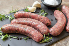 Raw Sausages on Slate with Herbs and  Spices Stock Image