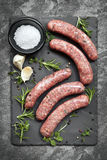 Raw Sausages on Slate Overhead View. Raw sausages on slate, with herbs and spices.  Overhead view Stock Image