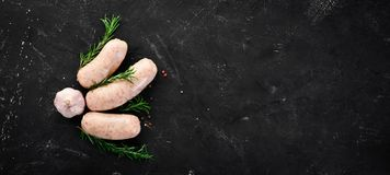Raw sausages with d herbs. Barbecue. spices anOn a black stone background. Raw sausages with spices and herbs. Barbecue. On a black stone background. Top view stock image