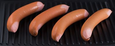 Raw sausages on the surface of the grill. The concept of traditional food Stock Photography