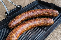 Raw sausages. Two raw sausages on a grill, ready for cooking Stock Photo