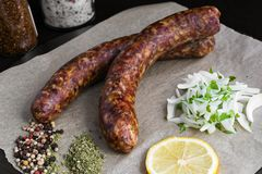 Raw sausages. Two raw sausages with spices, onion and lemon Royalty Free Stock Photography