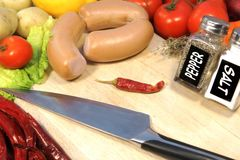 Raw Sausages, Vegetables and Big Chef's Knife on Wooden board Royalty Free Stock Photos