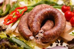Raw sausages,  with vegetables on wooden board Stock Images