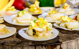 Raw Scallops topped with butter, garlic and parsley. Raw Scallops topped with butter, garlic and parsley on Chopping wood Royalty Free Stock Photo