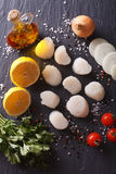 Raw scallops and vegetables for cooking close-up. vertical top v. Raw scallops and vegetables for cooking on a table close-up. vertical top view Royalty Free Stock Photo