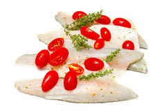 Raw sea bass fillets with cherry tomatoes on white. Some Raw sea bass fillets with cherry tomatoes on white stock photography