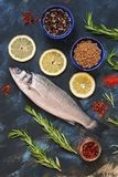 Raw sea bass fish on blue abstract background with lemon and spices. Raw sea bass fish on blue abstract background with lemon and spices Stock Photos