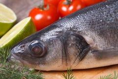 Raw sea bass fish on cutting board close-up horizontal. Raw sea bass fish on cutting board with vegetables close-up horizontal Royalty Free Stock Photos