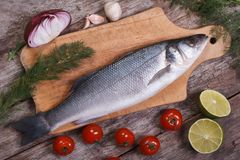 Raw sea bass fish on cutting board with vegetables top view Stock Photography