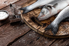 Raw sea bass fish. Fresh raw sea bass fish on wooden cutting board cooking concept on a dark wooden background Stock Photos