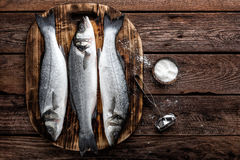 Raw sea bass fish. Fresh raw sea bass fish on wooden cutting board cooking concept on a dark wooden background top view Royalty Free Stock Images