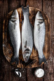 Raw sea bass fish. Fresh raw sea bass fish on wooden cutting board cooking concept on a dark wooden background top view Royalty Free Stock Photography