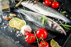 Raw sea bass fish with spices. And ingredients, ready for cooking, dark concrete background copy space stock photo