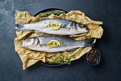 Raw sea bass on Kraft paper with rosemary, thyme and lemon. Black background, top view. royalty free stock photography