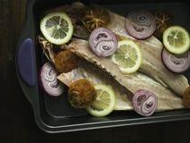 Raw sea bass with lemon, onion and tomato ready Stock Photos