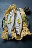 Raw sea bass with rosemary, thyme and lemon. Black background, top view. stock image