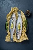 Raw sea bass with rosemary, thyme and lemon. Black background, top view. royalty free stock photos