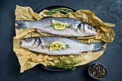 Raw sea bass with rosemary, thyme and lemon. Black background, top view. royalty free stock photo