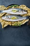 Raw sea bass with rosemary, thyme and lemon. Black background, top view, space for text. stock photos