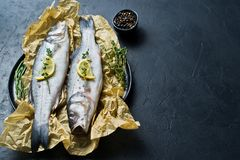 Raw sea bass with rosemary, thyme and lemon. Black background, top view, space for text. stock image