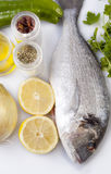 Raw sea bream fish with some ingredients. Over white background Stock Images