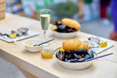 Raw seafood - mussels, oysters on a wooden table with a glass of. Champagne, an outdoor food market Stock Photos