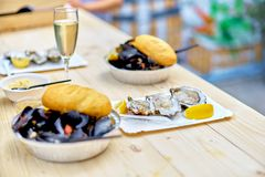 Raw seafood - mussels, oysters on a wooden table with a glass of. Champagne, an outdoor food market Royalty Free Stock Photography