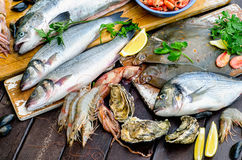 Raw seafood on wooden board. Stock Photo