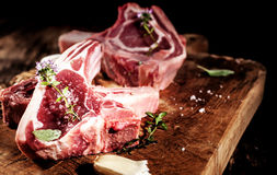Raw Seasoned Lamb Filets on Rustic Wooden Board Royalty Free Stock Images