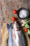 Raw seebass fish. Two raw uncooked seebass fish on baking paper with sea salt, dry herbs and vegetables over old wooden background. Top view Stock Photo