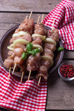 Raw shashlik ready to cook on plate. Raw chicken meat on skewers ready to cook on plate on aged wooden background. Selective focus. Rustic style Stock Images