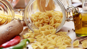 Raw shells pasta, chilli peppers and olive oil. Raw shells pasta, chilli peppers, olive oil and a rolling pin Royalty Free Stock Image