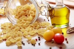 Raw shells pasta, tomatoes and olive oil. On a table Royalty Free Stock Image