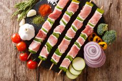 Raw shish kebab with green pepper on skewers close-up and vegetables, herbs. Horizontal top view. Raw shish kebab with green pepper on skewers close-up and stock images