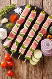 Raw shish kebab with green pepper on skewers close-up and vegetables, herbs. Vertical top view. Raw shish kebab with green pepper on skewers close-up and stock photo